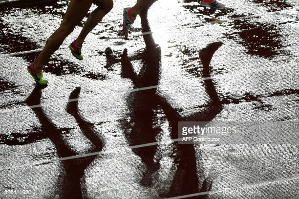 Shadows of athletes are pictured on the track as they compete in the women's 3000m steeplechase athletics event at the 2017 IAAF World Championships...