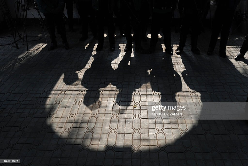 Shadows of Bangladeshi police officials are seen as they stand guard at the International Crimes Tribunal court premises in Dhaka on January 21, 2013. Bangladesh's controversial war crimes court sentenced to death a top Islamic televangelists for genocide and other atrocities during the country's 1971 liberation struggle against Pakistan, a prosecutor said. Maolana Abul Kalam Azad who has been on the run for about a year is the first person to have been convicted by the controversial International Crimes Tribunal, created by the country's secular government to try suspected war criminals. AFP PHOTO/Munir uz ZAMAN