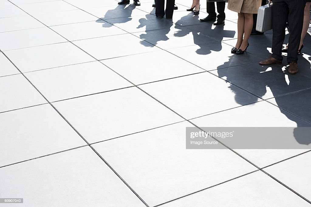 Shadows of businesspeople standing : Stock Photo