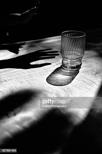 Shadows of human hands and empty cup