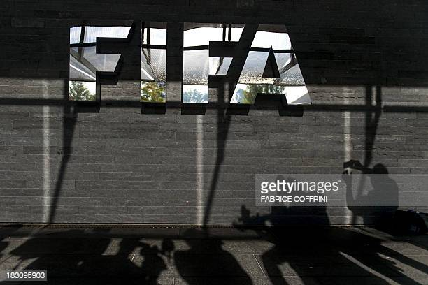 Shadows of journalists are seen next to a logo of the football's world governing body FIFA after a press conference on October 4 2013 at ist...