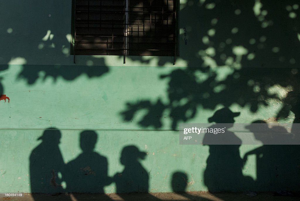 Shadows of members of the Mara Salvatrucha gang lie on a wall as they attend the official ceremony to declare the the city of Quezaltepeque a peace zone of 'Sanctuary City' for gang violence on January 31, 2013 in Quezaltepeque, 25 kms west of San Salvador. Leaders of the Mara Salvatrucha (MS-13) and Barrio 18 signed a document to assure the continuation of the peace process and support of the truce they started on 2012, which has already lowered the average daily murder rate from 14 to 5. AFP PHOTO/ Juan CARLOS