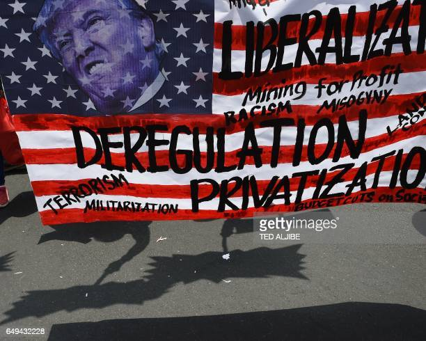 Shadows of members of women's group Gabriela holding placards are seen next to a mockup US flag with a portrait of President Donald Trump during a...