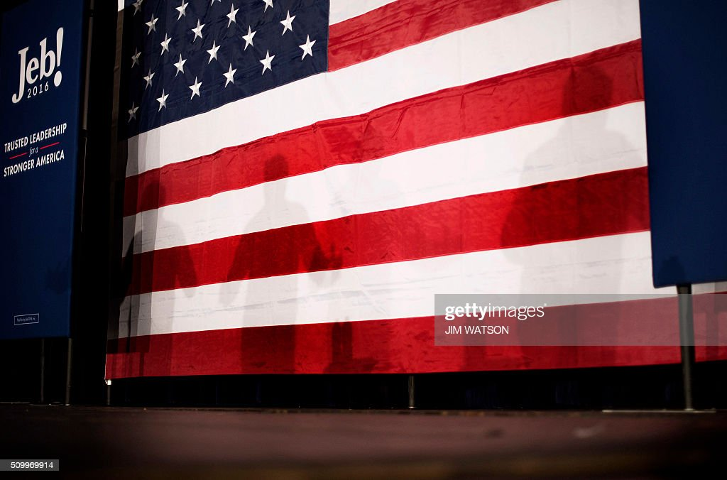 Shadows of Republican presidential candidate Jeb Bush stand against the US flag during a town hall in Fountain Inn, South Carolina, on February 13, 2016. / AFP / JIM WATSON