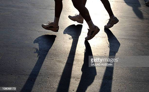 Shadows of the participants running in the Standard Chartered Mumbai Marathon 2011 race are seen on the race course in Mumbai on January 16 2011...