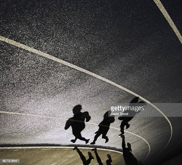 Shadows of three people running