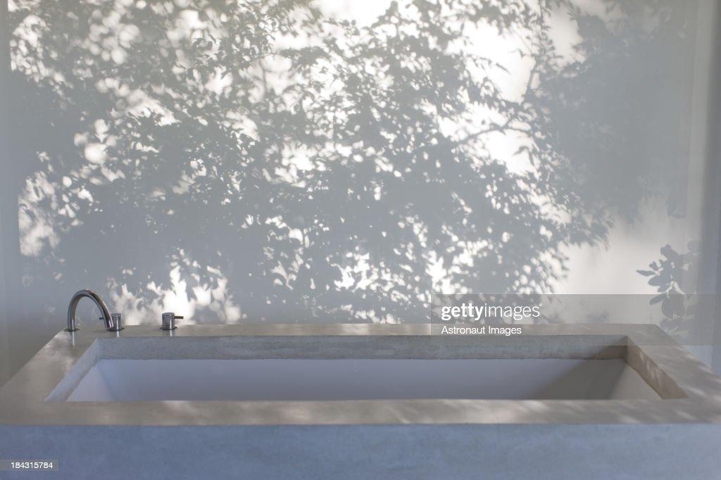 Shadows of trees on curtain behind bathtub : Stock Photo