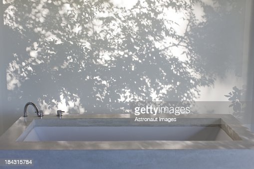 Shadows of trees on curtain behind bathtub