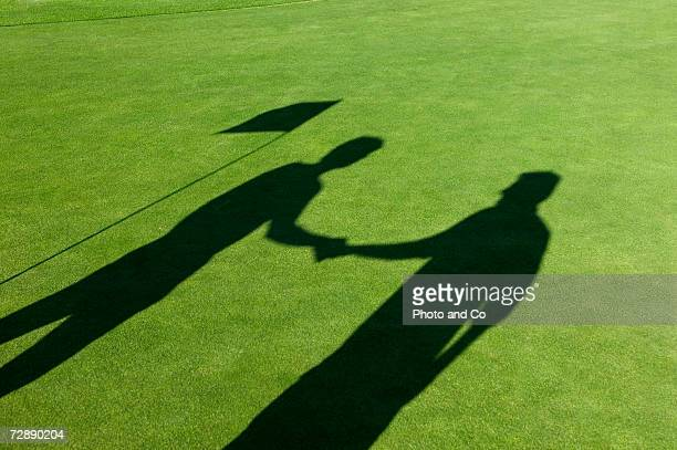Shadows of two male golfers shaking hands on golf course