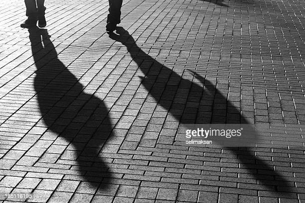 Shadows Of Two People Walking On The Street