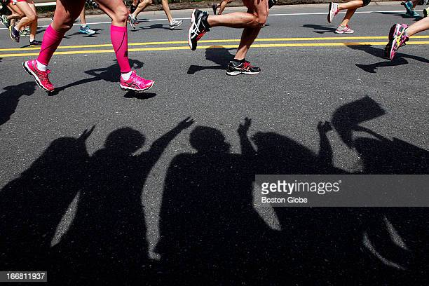 Shadows of Wellesley students waved alongside runners The 117th Annual Boston Marathon makes its way by Wellesley College on Route 135 in Wellesley...