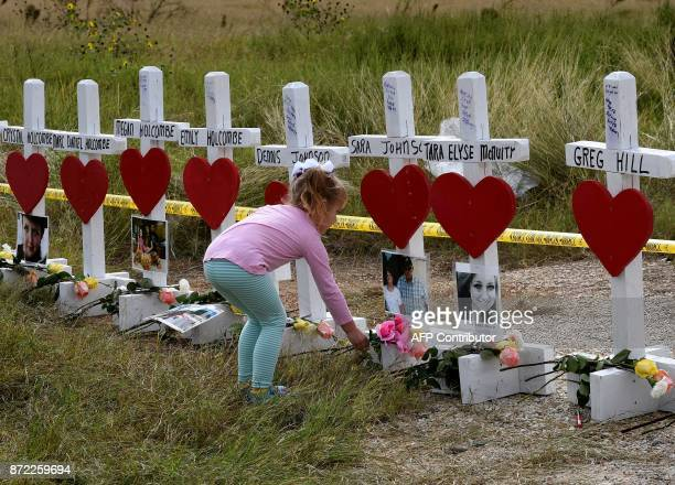 Shaelyn Gisler prepares to leave flowers on crosses named for the victims outside the First Baptist Church which was the scene of the mass shooting...