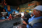 Shafiq alTal sits with his family inside his tent in the Palestinian village of Khirbet Zanuta located in the hills south of the West Bank city of...