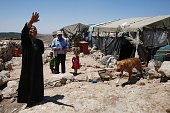 Shafiq alTal stands with his family outside his tent in the Palestinian village of Khirbet Zanuta located in the hills south of the West Bank city of...