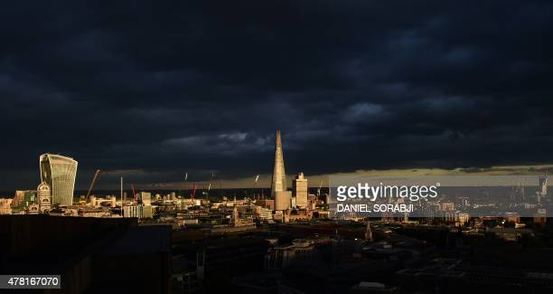 A shaft of light picks out the Shard tower and the WalkieTalkie at 20 Fenchurch Street as it travels across the city at sunset in London on June 22...