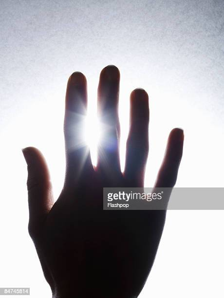 Shafts of sunlight pouring through fingers