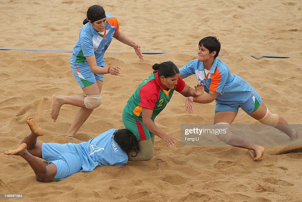 Shahanaj Parvin Maleka (C) of Bangladesh is held by Marshalmary Savariyappan (L) of India during the Beach Kabaddi Women's Team Group A match between India and Bangladesh on Day 4 of the 3rd Asian Beach Games Haiyang 2012 at Fengxiang Beach on June 20, 2012 in Haiyang, China.