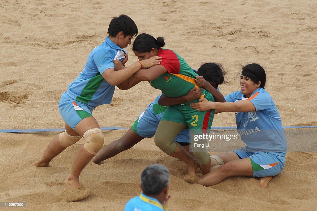 Shahanaj Parvin Maleka (C) of Bangladesh is held by Randeep Kaur Khehra (R) of India during the Beach Kabaddi Women's Team Group A match between India and Bangladesh on Day 4 of the 3rd Asian Beach Games Haiyang 2012 at Fengxiang Beach on June 20, 2012 in Haiyang, China.