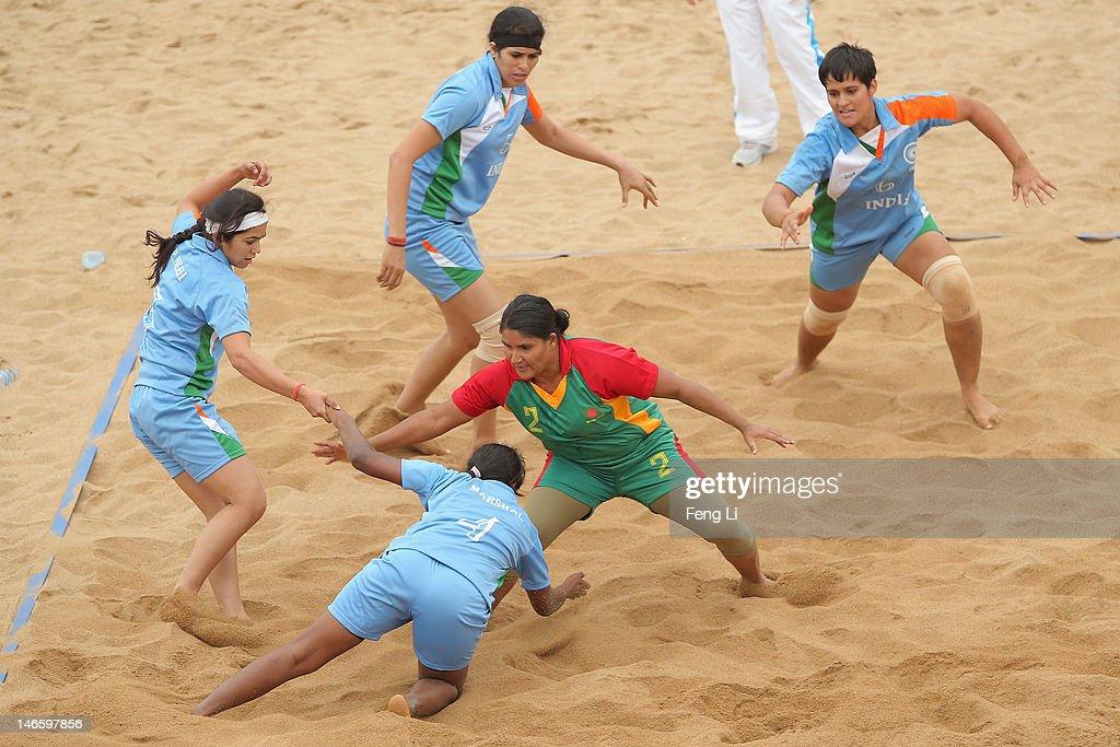 Shahanaj Parvin Maleka (R) of Bangladesh is tackled as she competes during the Beach Kabaddi Women's Team Group A match between India and Bangladesh on Day 4 of the 3rd Asian Beach Games Haiyang 2012 at Fengxiang Beach on June 20, 2012 in Haiyang, China.