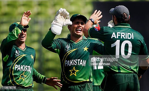 Shahid Afridi of Pakistan celebrates with team mates Kamran Akmal and Saeed Ajmal after taking the catch to dismiss Chris Gayle of West Indies off...