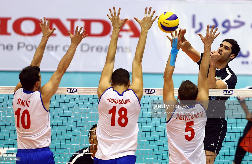 Shahram Mahmoudi of Iran in action against Milos Nikic Marko Podrascanin and Vlado Petkovic of Serbia during the Volleyball World League match...