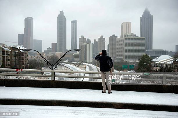 Shaka Berry pauses to photograph the Atlanta skyline as he walks to a friend's house on February 12 in Atlanta Georgia Driving conditions were...