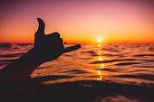 Shaka symbol and red sunset at sea. Lifestyle photo