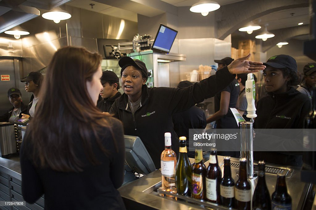 A Shake Shack employee, center, gestures as she speaks with a customer, left, at the counter inside the company's new burger restaurant in London, U.K., on Tuesday, July 2, 2013. Shake Shack, opening in London's Covent Garden this week, started as a hotdog cart in New York's Madison Square Park, and has outlets in six U.S. states as well as in the Middle East and Turkey. Photographer: Simon Dawson/Bloomberg via Getty Images