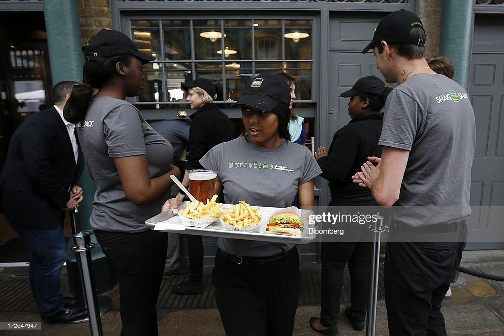 A Shake Shack employee takes a tray of food to a customer outside the company's new burger restaurant in London, U.K., on Tuesday, July 2, 2013. Shake Shack, opening in London's Covent Garden this week, started as a hotdog cart in New York's Madison Square Park, and has outlets in six U.S. states as well as in the Middle East and Turkey. Photographer: Simon Dawson/Bloomberg via Getty Images