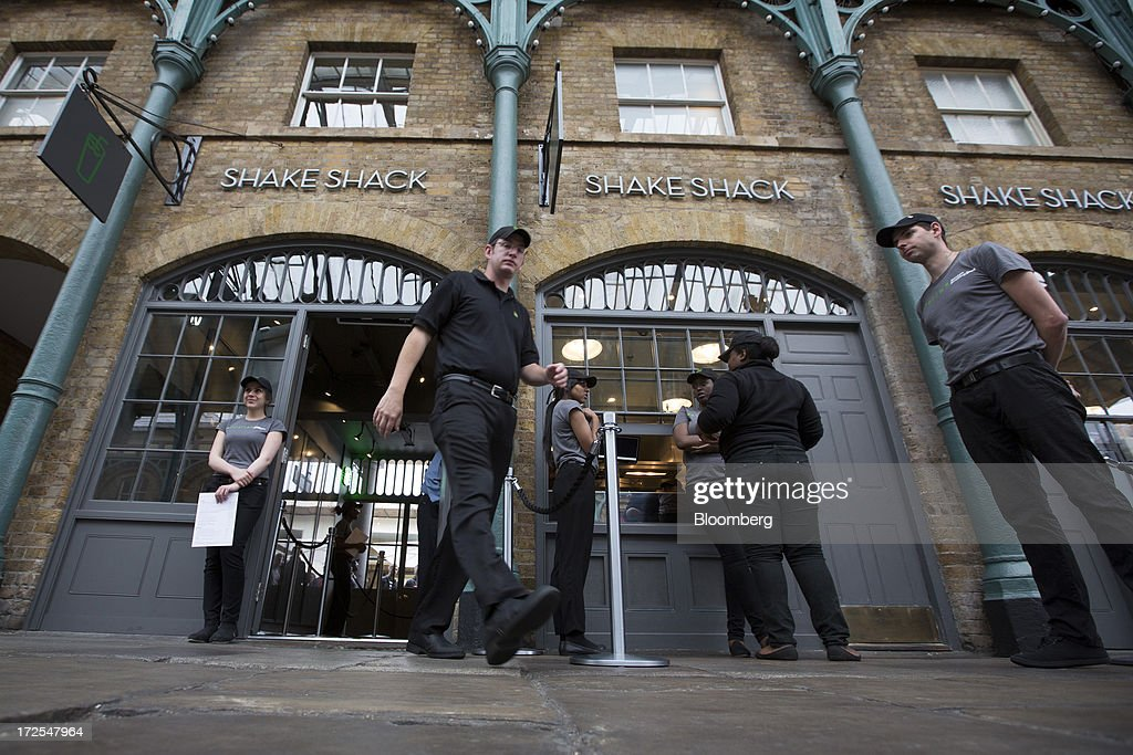 Shake Shack employees stand outside the company's new burger restaurant in London, U.K., on Tuesday, July 2, 2013. Shake Shack, opening in London's Covent Garden this week, started as a hotdog cart in New York's Madison Square Park, and has outlets in six U.S. states as well as in the Middle East and Turkey. Photographer: Simon Dawson/Bloomberg via Getty Images