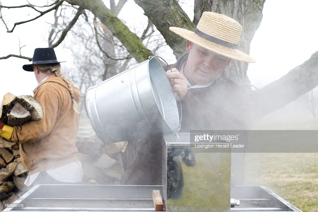 Shaker Village Historic Interpreter Philip McIntosh, of Harrodsburg, center, pours sap from a sap pail into the evaporator as Shaker Village Historic Interpreter, Mark Ross, of Harrodsburg, selects firewood at Shaker Village in Harrodsburg, Kentucky, March 1, 2013. 'We are constantly adding and taking it off [of the evaporator,] Ross explained. 'As it gets brown we pull it for the final cooking.'