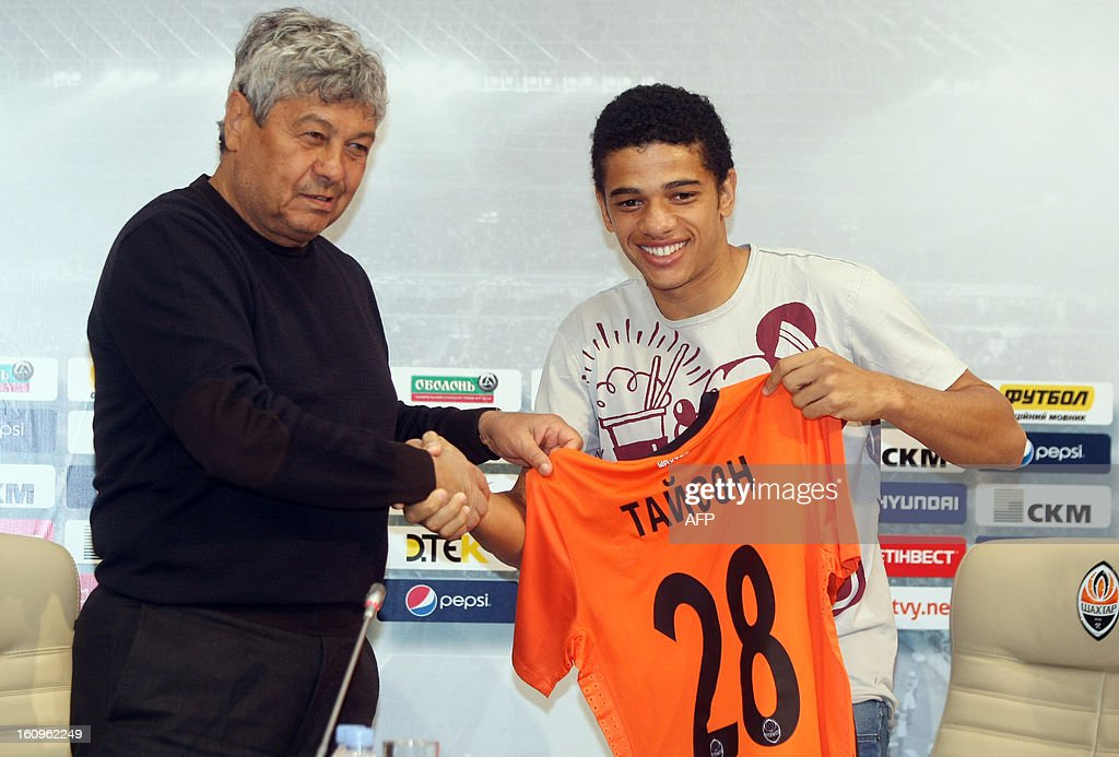 FC Shakhtar coach Mircea Lucescu (L) shakes hands FC Shakhtar's new Brazilian forward Taison, holdsing a his new team's jersey, on February 8, 2013 during his presentation in Donetsk. Taison, a former football player of Ukrainian FC Metalist, signed a five-year contract with FC Shakhtar.