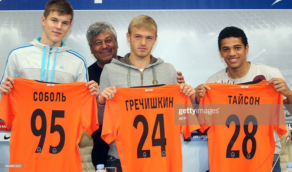 FC Shakhtar coach Mircea Lucescu (2nd L, back) smiles as new players Eduard Sobol (L) and Dmitriy Grechishkin (C), graduates of FC Shakhtar Football School, and Brazilian forward Taison (R) hold up thier jerseys on February 8, 2013 during his presentation in Donetsk. Taison, a former football player of Ukrainian FC Metalist, signed a five-year contract with FC Shakhtar. AFP PHOTO/ ALEXANDER KHUDOTEPLY