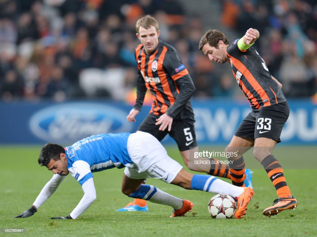 FC Shakhtar Donetsk's Darijo Srna (R) and Olexandr Kucher (C) fight for the ball with Real Sociedads Carlos Vela (down) during their UEFA Champions League Group A football match in Donetsk on November 27, 2013.