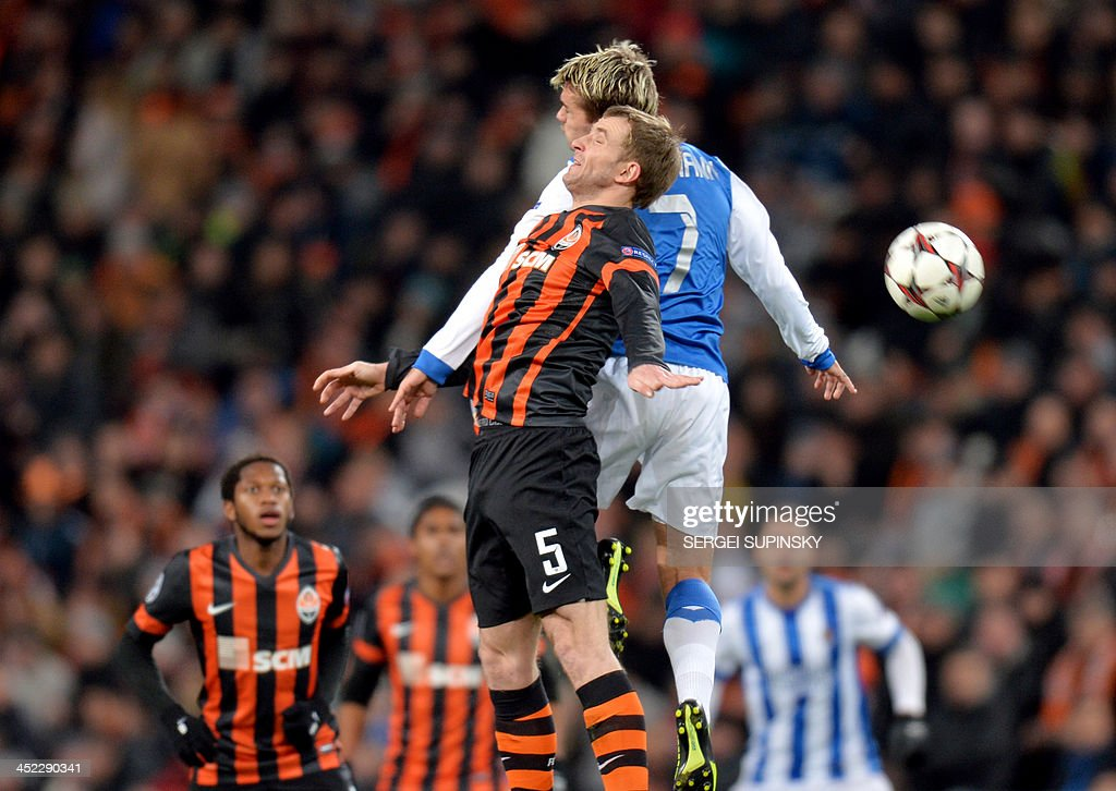 FC Shakhtar Donetsk's Olexandr Kucher (L) fights for the ball with Real Sociedads David Zurutuza (R) during their UEFA Champions League Group A football match in Donetsk on November 27, 2013.