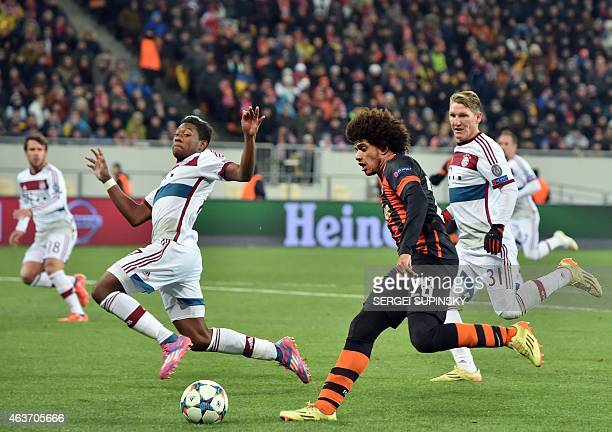 FC Shakhtar Donetsk's Taison and Bayern Munich's David Alaba fight for the ball on February 17 2015 during a UEFA Champions League football match FC...