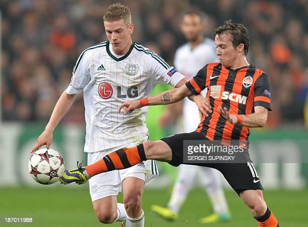 Shakhtar's Brazilian midfielder Bernard vies for the ball with Leverkusen's German midfielder Lars Bender the UEFA Champions League Group A football...