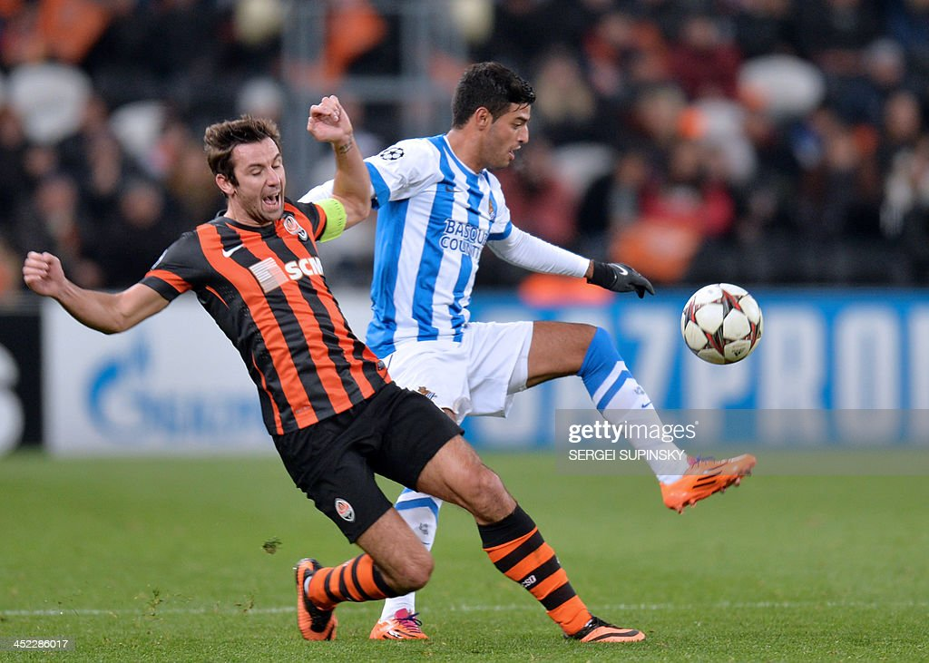 FC Shakhtar's Darijo Srna and Real Sociedads Carlos Vela (L) fight for the ball during their UEFA Champions League Group A football match in Donetsk on November 27, 2013.