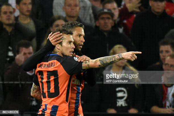 Shakhtar's midfielder Bernard celebrates with a teammate after scoring a goal during the UEFA European Champions League Group F football match...