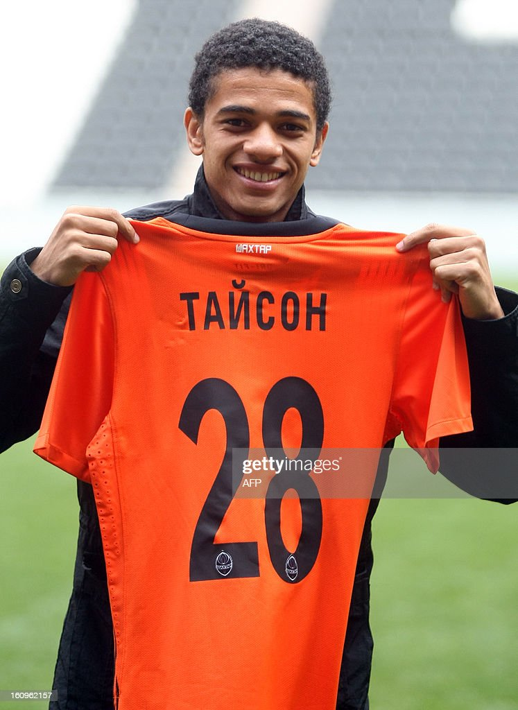 FC Shakhtar's new Brazilian forward Taison holds a New team's jersey on February 8, 2013 during his presentation in Donetsk. Taison, a former football player of Ukrainian FC Metalist, signed a five-year contract with FC Shakhtar. KHUDOTEPLY