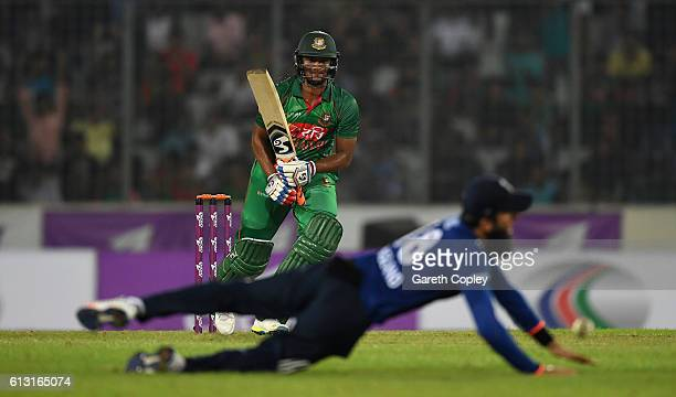 Shakib Al Hasan of Bangladesh hits past Moeen Ali of England during the 1st One Day International match between Bangladesh and England at ShereBangla...