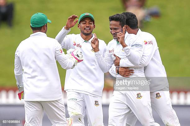 Shakib Al Hasan of Bangladesh is congratulated after taking the wicket of Tom Latham of New Zealand during day four of the First Test match between...