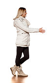 young beautiful woman in winter clothes making shaking gesture