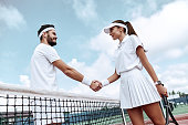 Shaking hands after good game. Man and woman in wristband shaking hands upon the tennis net