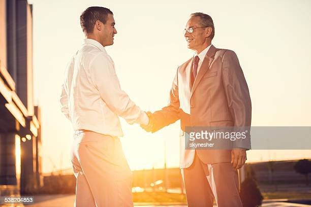 Se serrant la main au coucher du soleil.