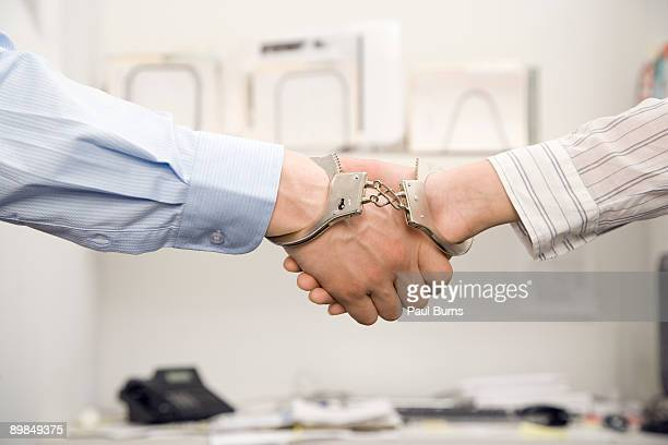Shaking Hands in Office With Handcuffs