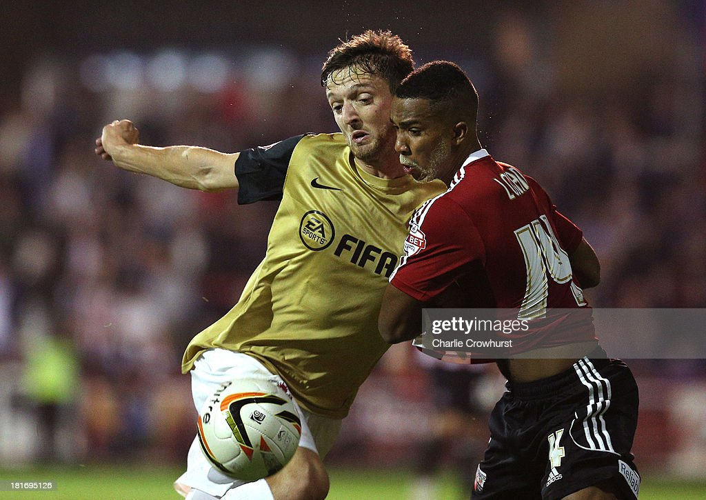 Shaleum Logan of Brentford brings down David Mooney of Leyton Orient to concede a penalty during the Sky Bet League Once match between Brentford and Leyton Orient at Griffin Park on September 23, 2013 in Brentford, England.
