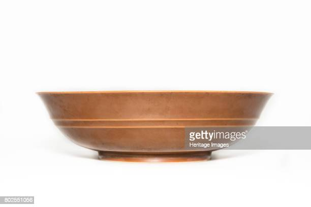 A shallow bowl with slightly outturned rim and two low ridges circling the exterior covered with a deep cafe au lait monochrome glaze The base has a...