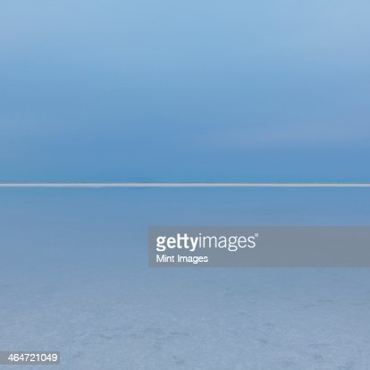 Shallow water over the surface at the Bonneville Salt Flats near Wendover, at dusk. The land meeting the sky on the horizon, and a white line of salt crystals. : Stock Photo