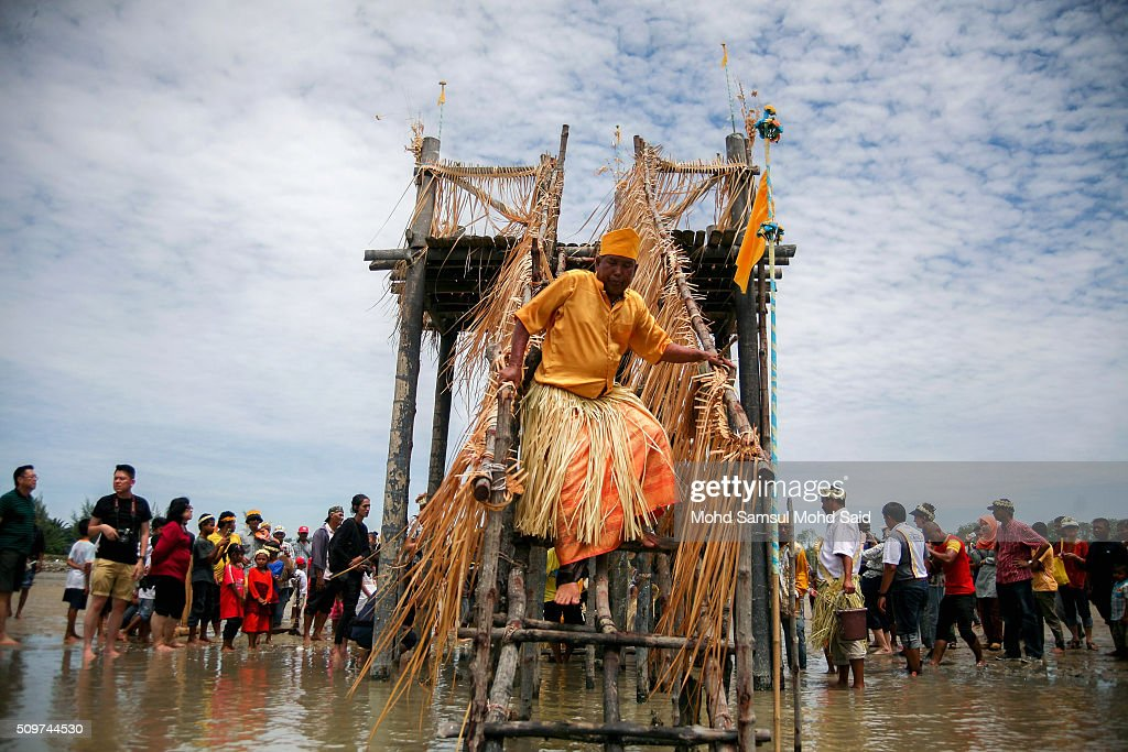 A shaman of the Mah Meri tribe steps down from the shrine as they offer a prayer to the sea at Pulau Carey, Straits of Malacca beach on February 12, 2016 in Pulau Carey, Malaysia. Every year, the indigenous people of Mah Meri village, located in Pulau Carey, about 140 km (87 miles) southwest of Kuala Lumpur, perform the 'Puja Pantai' ritual prayer and 'Main Jo-oh' dance to appease the spirits of the seas and celebrate the New Year.